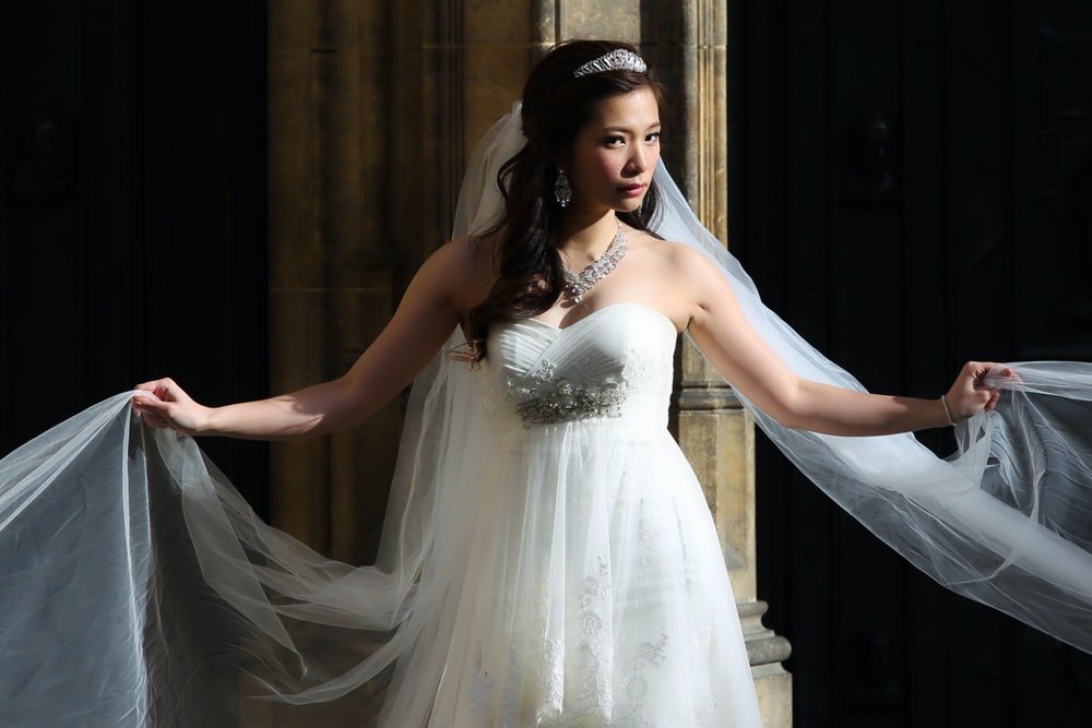 woman in white wedding dress standing on stairs
