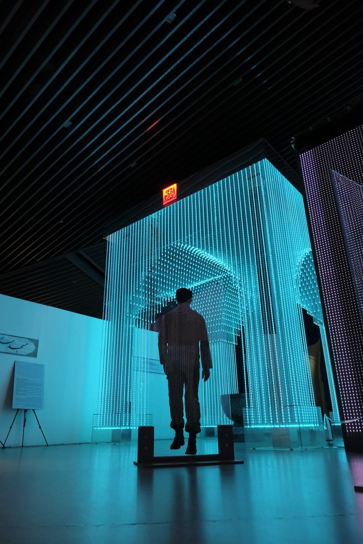 man in black jacket standing on blue lighted room