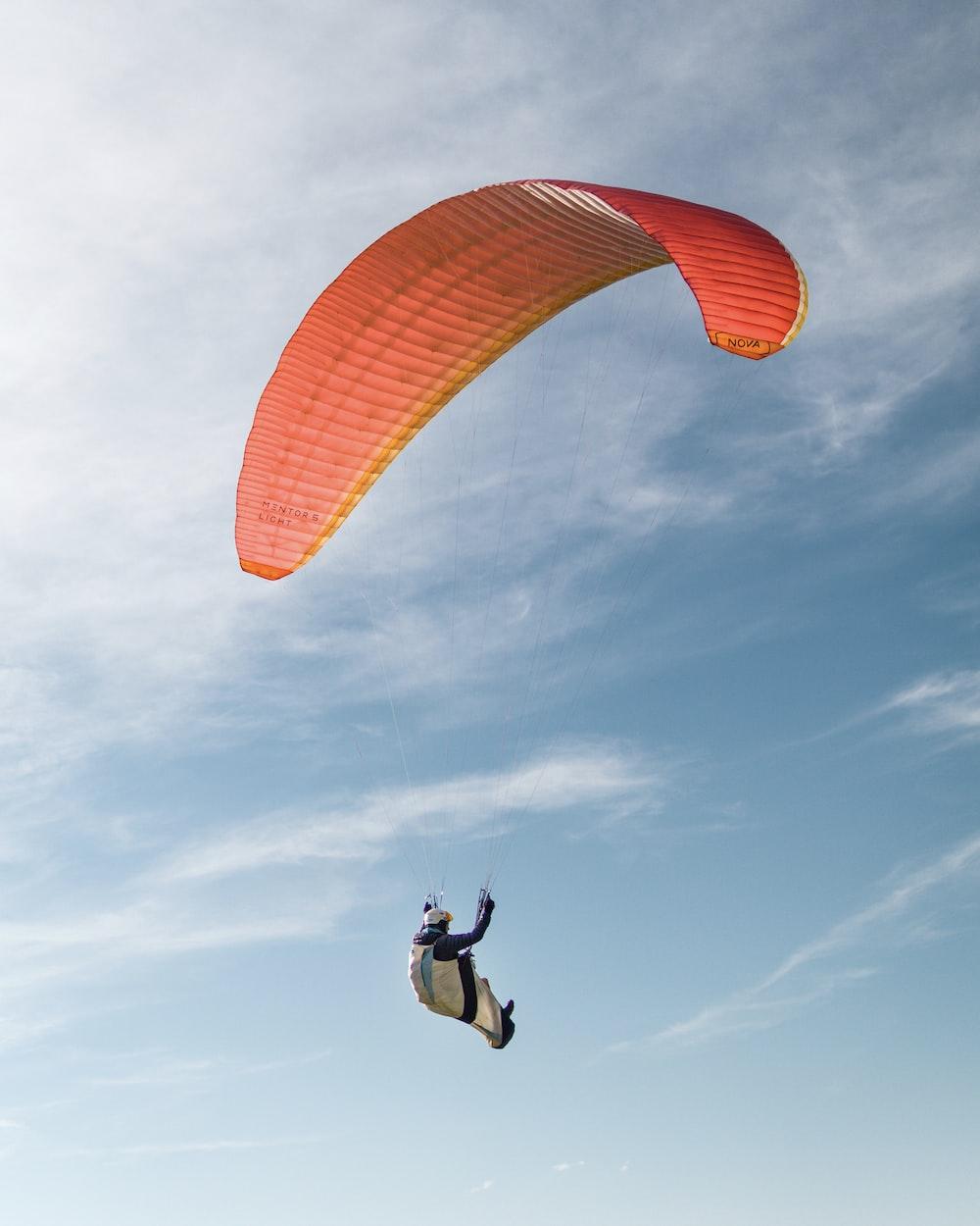 person in orange parachute under blue sky during daytime
