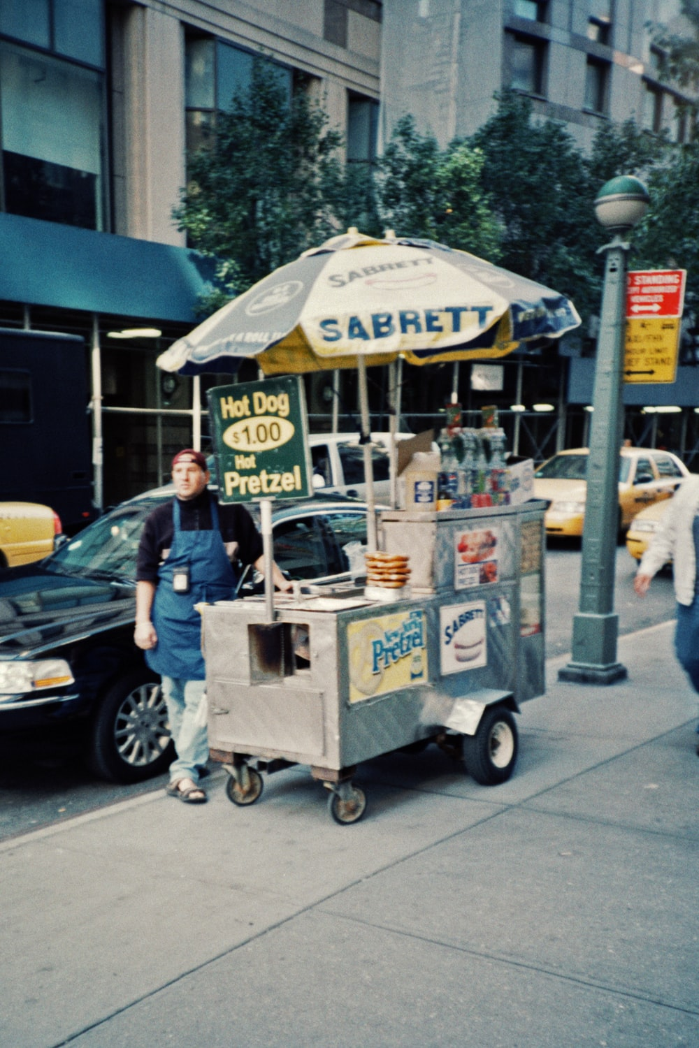 man in blue t-shirt and blue denim jeans standing beside food cart