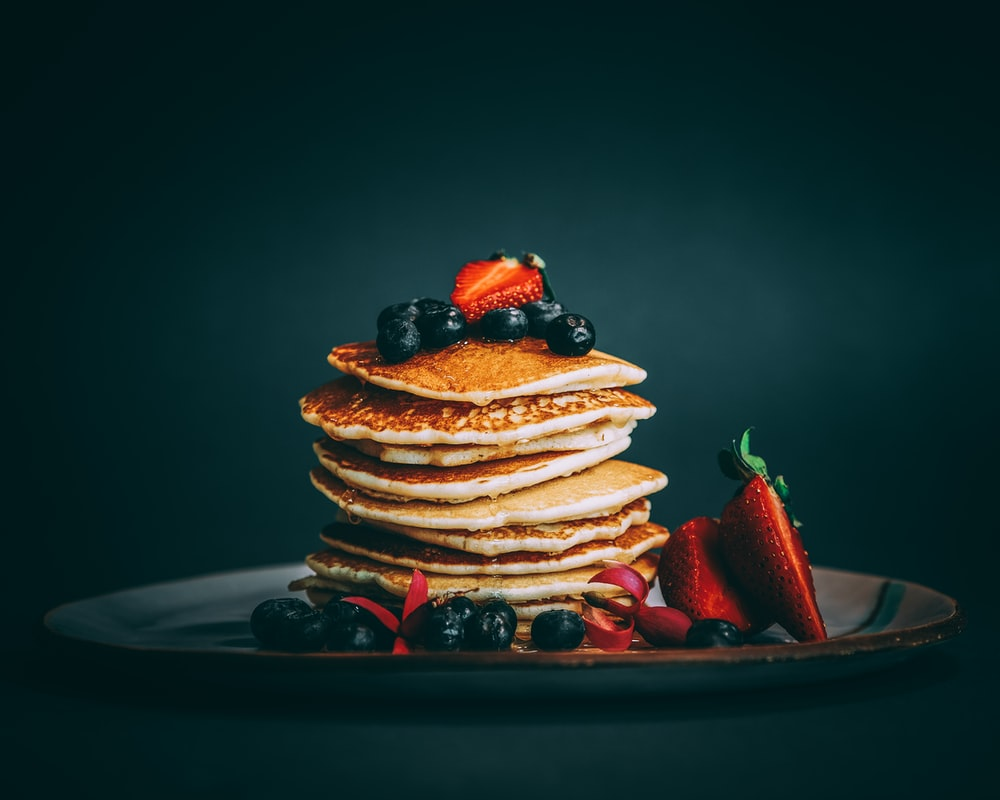 pancakes with strawberries and blueberries on top