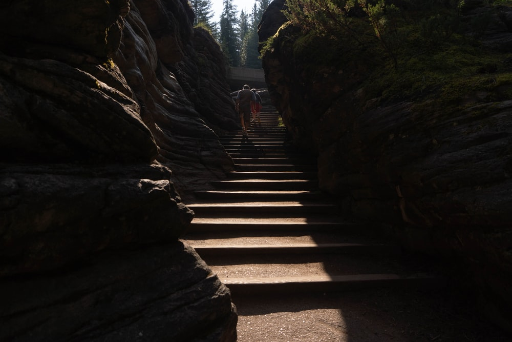people walking on stairs between rocky mountains during daytime