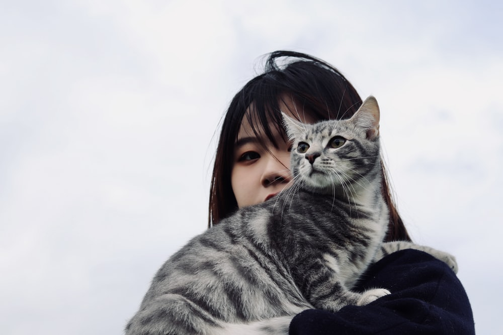 woman in black jacket holding silver tabby cat