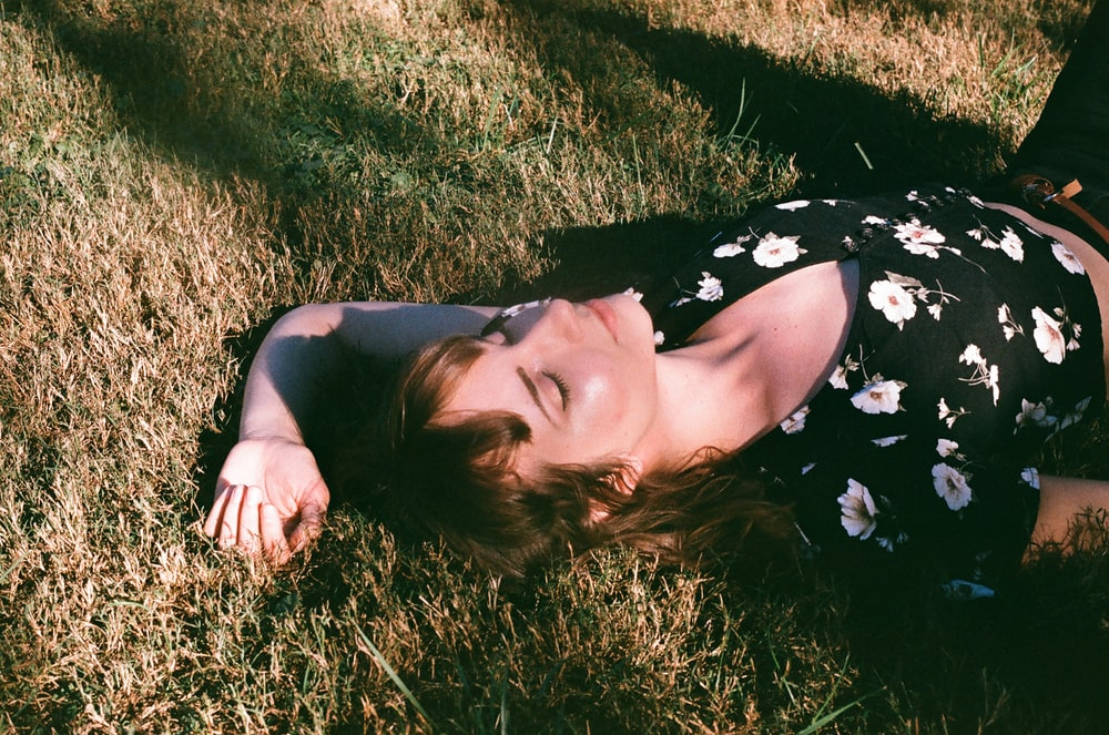 woman in black and white floral dress lying on green grass field