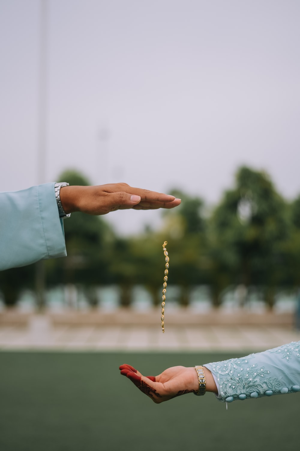 person holding brown and white beaded necklace