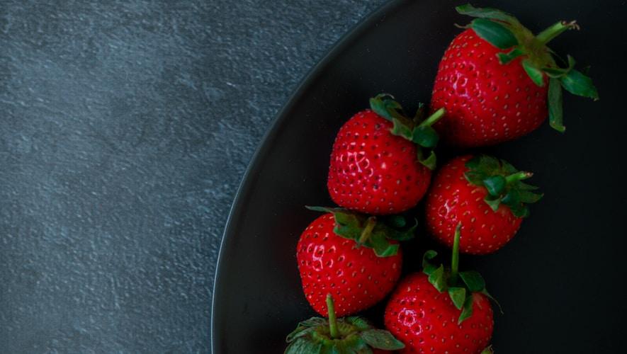 red strawberries on black ceramic bowl