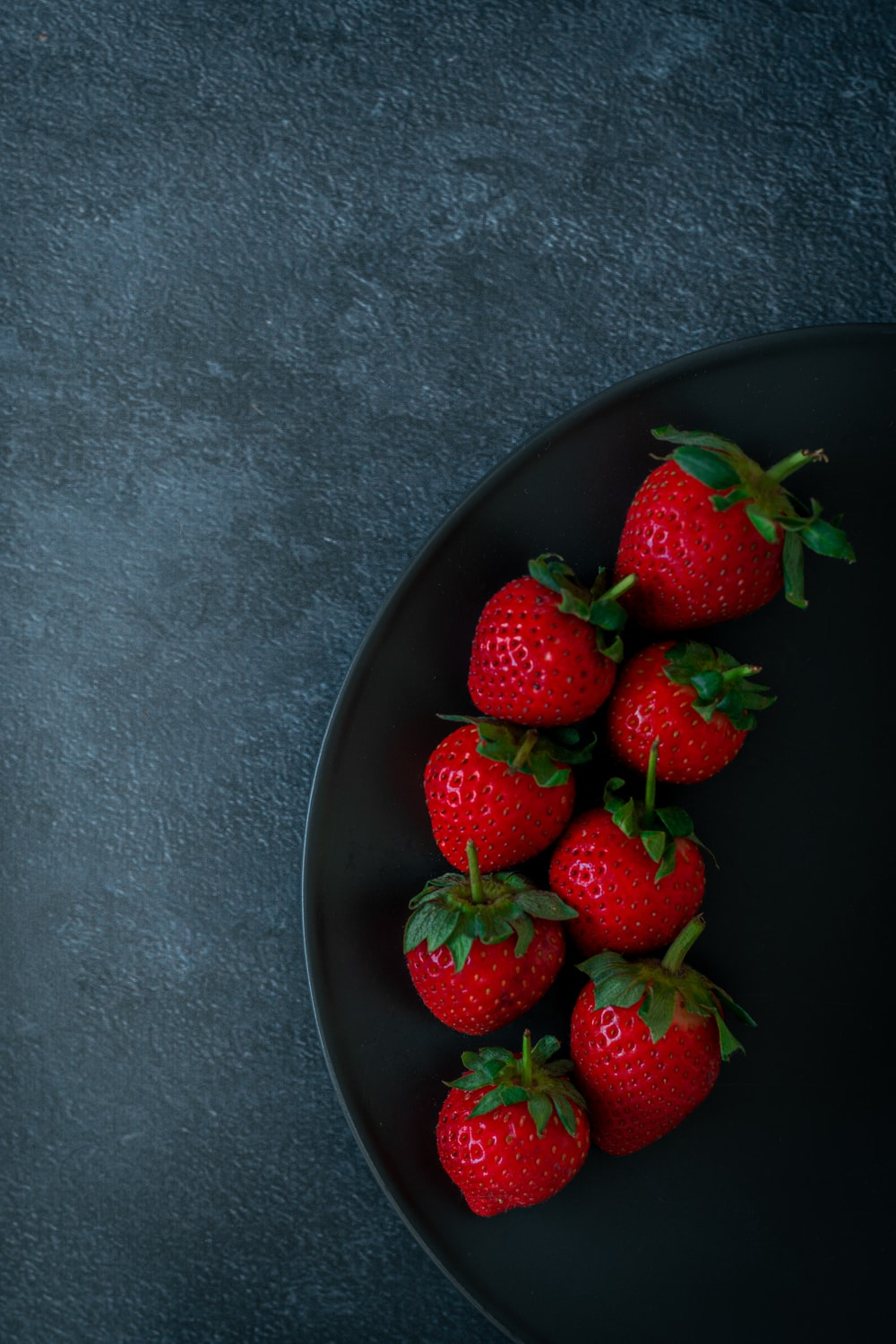 red strawberries on black ceramic bowl