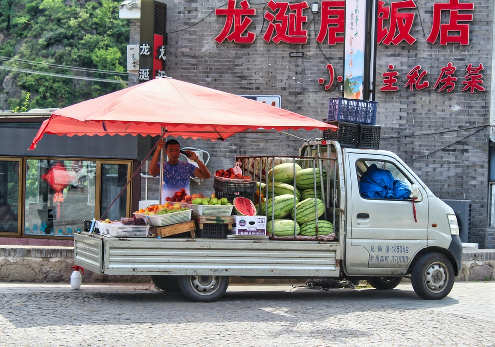 white van with fruits and vegetables on top