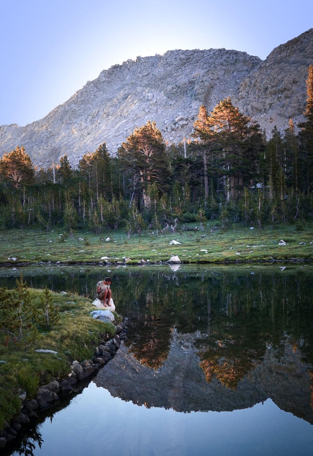 person sitting on rock near lake during daytime