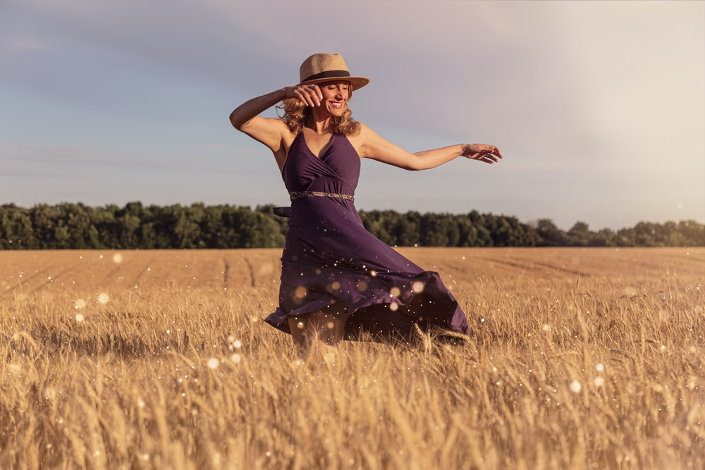woman in brown sun hat standing on wheat field during daytime