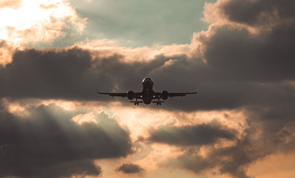 silhouette of airplane under cloudy sky during daytime