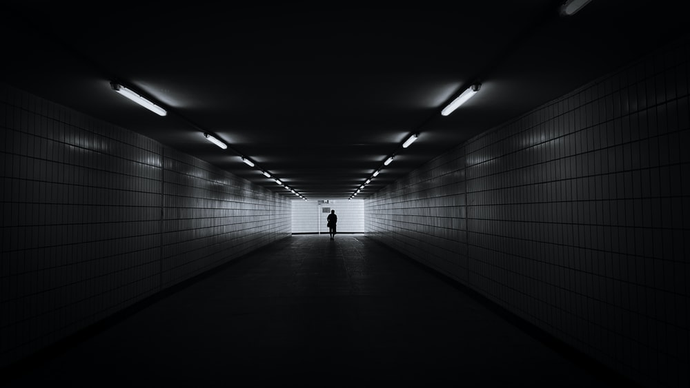 person in white shirt walking on tunnel