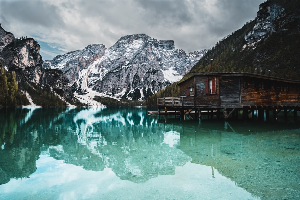 brown wooden house on lake near snow covered mountain during daytime