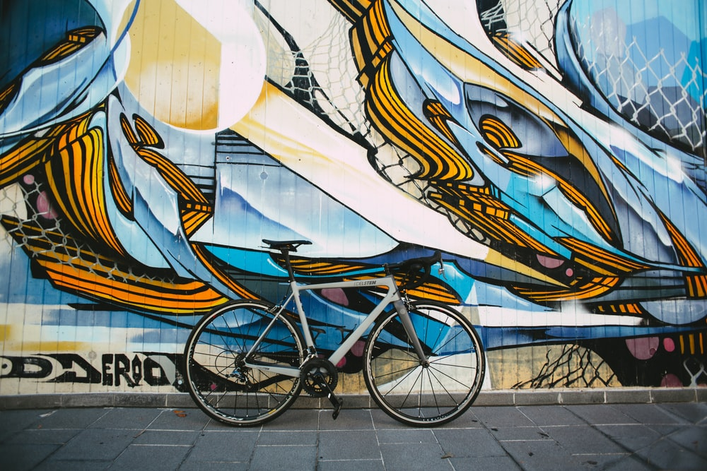 blue city bike parked beside white blue and brown wall
