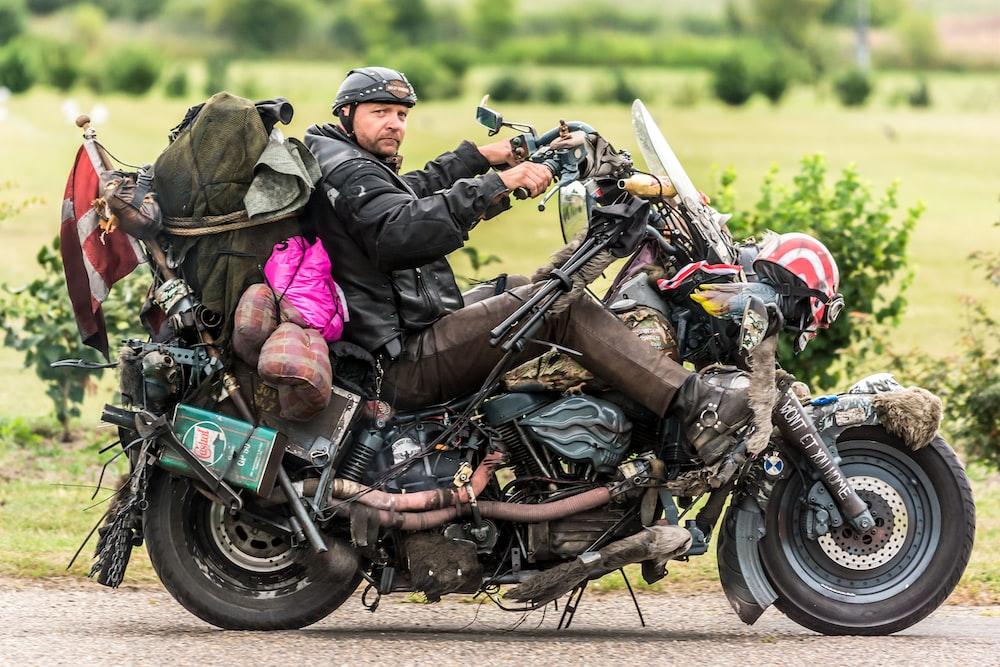 man in black leather jacket riding on black motorcycle during daytime