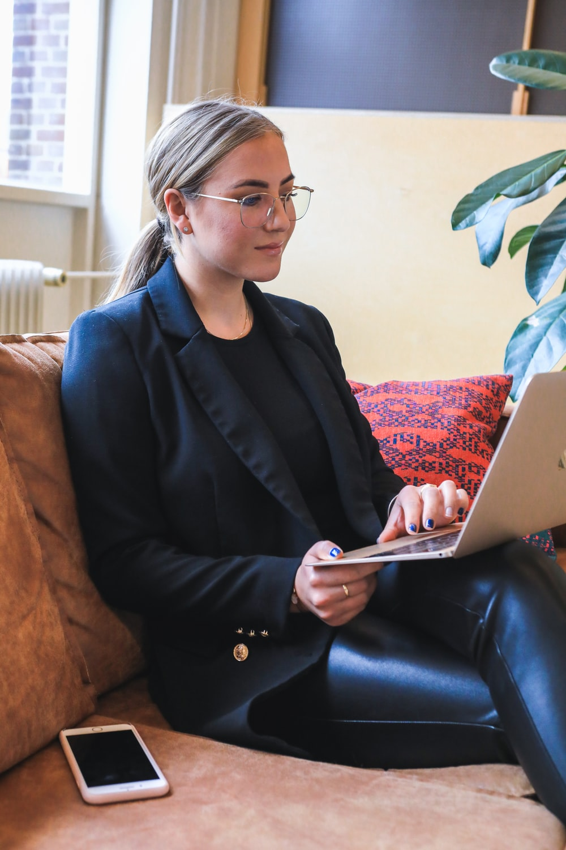 woman in black blazer using macbook