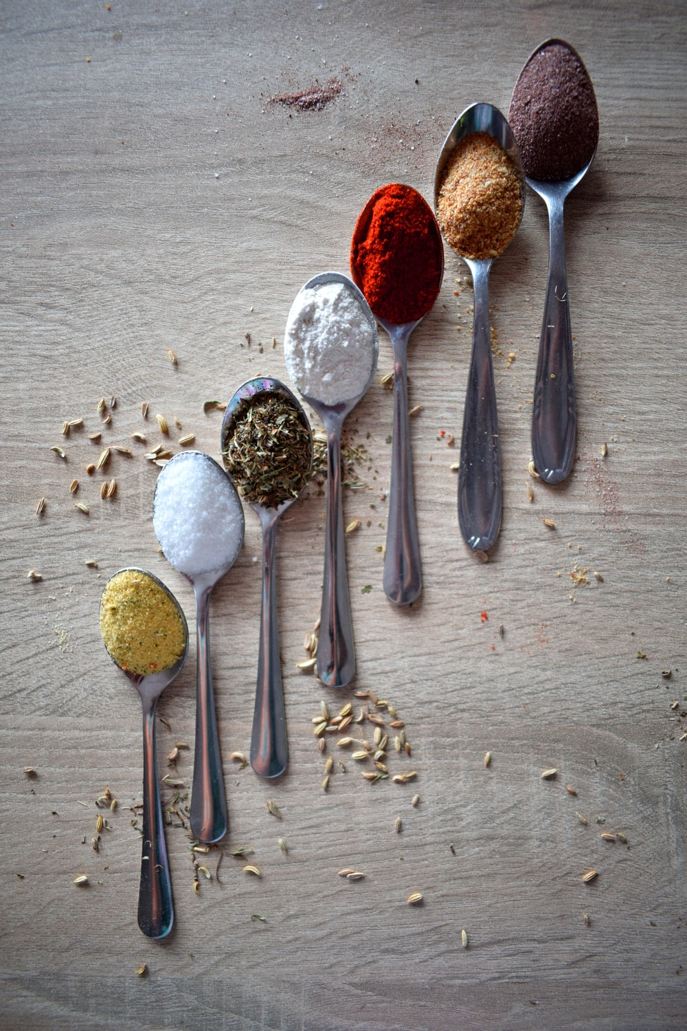 stainless steel spoons and spices on gray wooden table