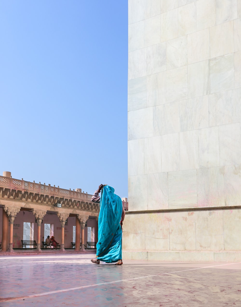 woman in green hijab standing near white concrete building during daytime