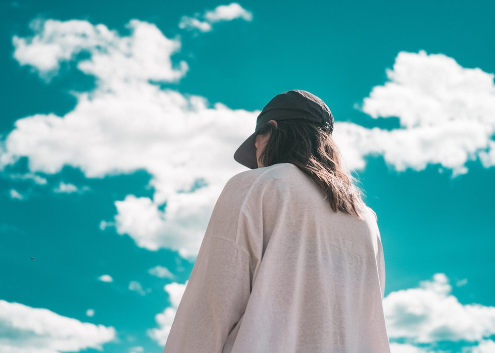 woman in white long sleeve shirt and black cap under white clouds and blue sky during