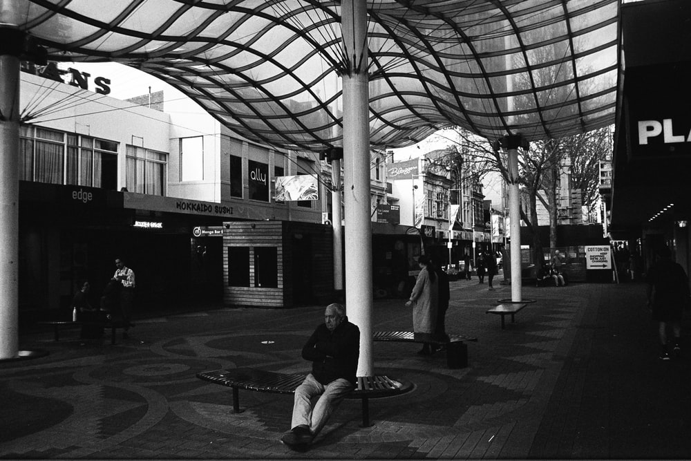 grayscale photo of man sitting on bench near post lamp