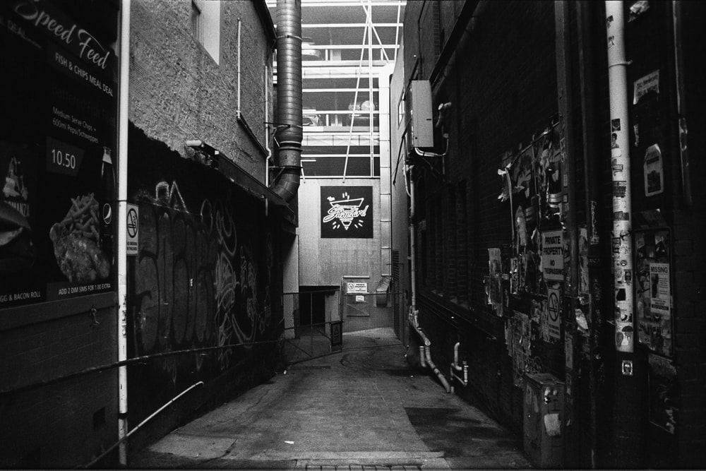 grayscale photo of hallway with graffiti