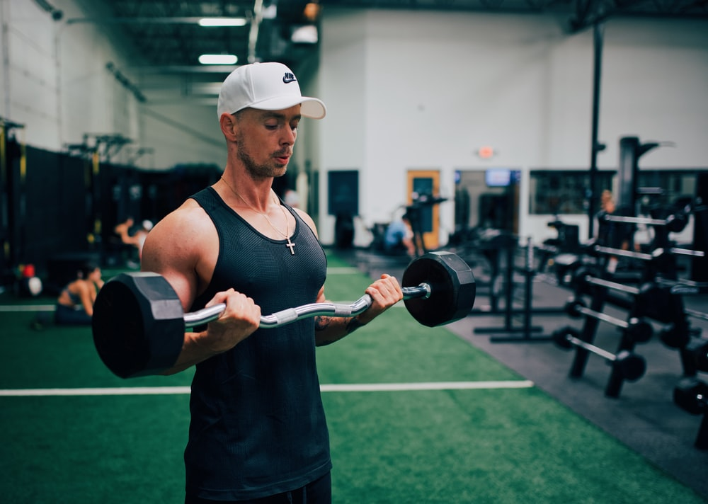 man in black tank top and white cap holding black and gray dumbbell
