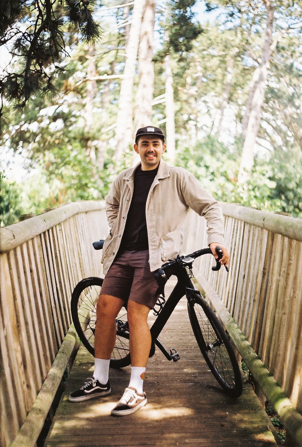 man in brown jacket and black shorts riding black bicycle
