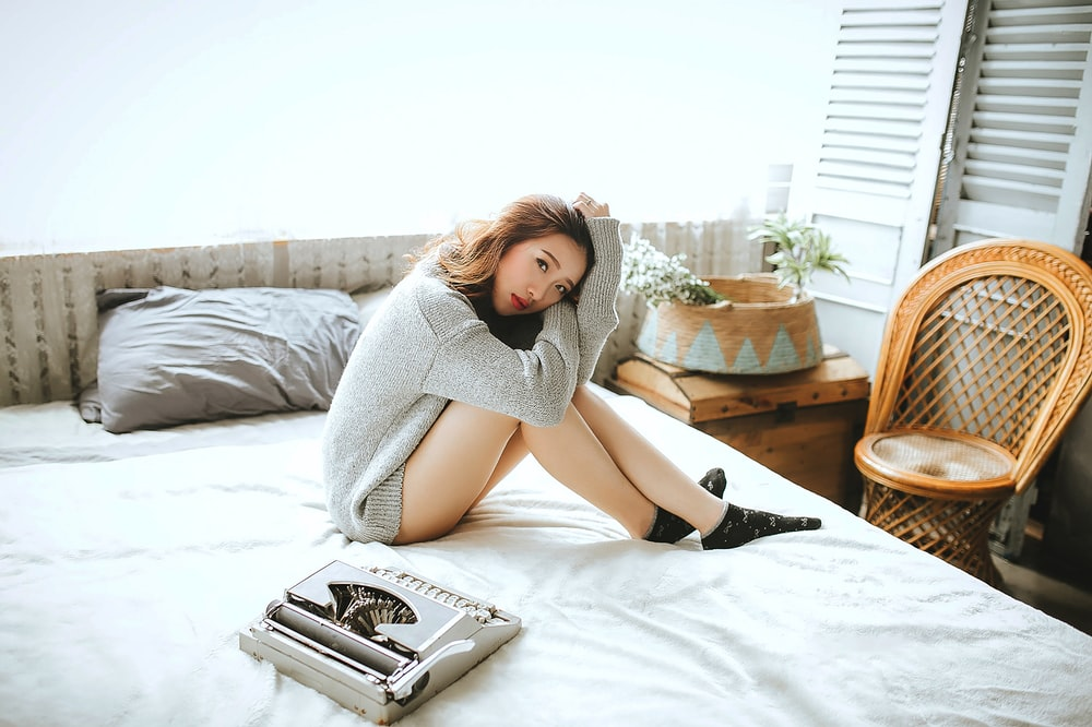 woman in gray long sleeve shirt lying on bed