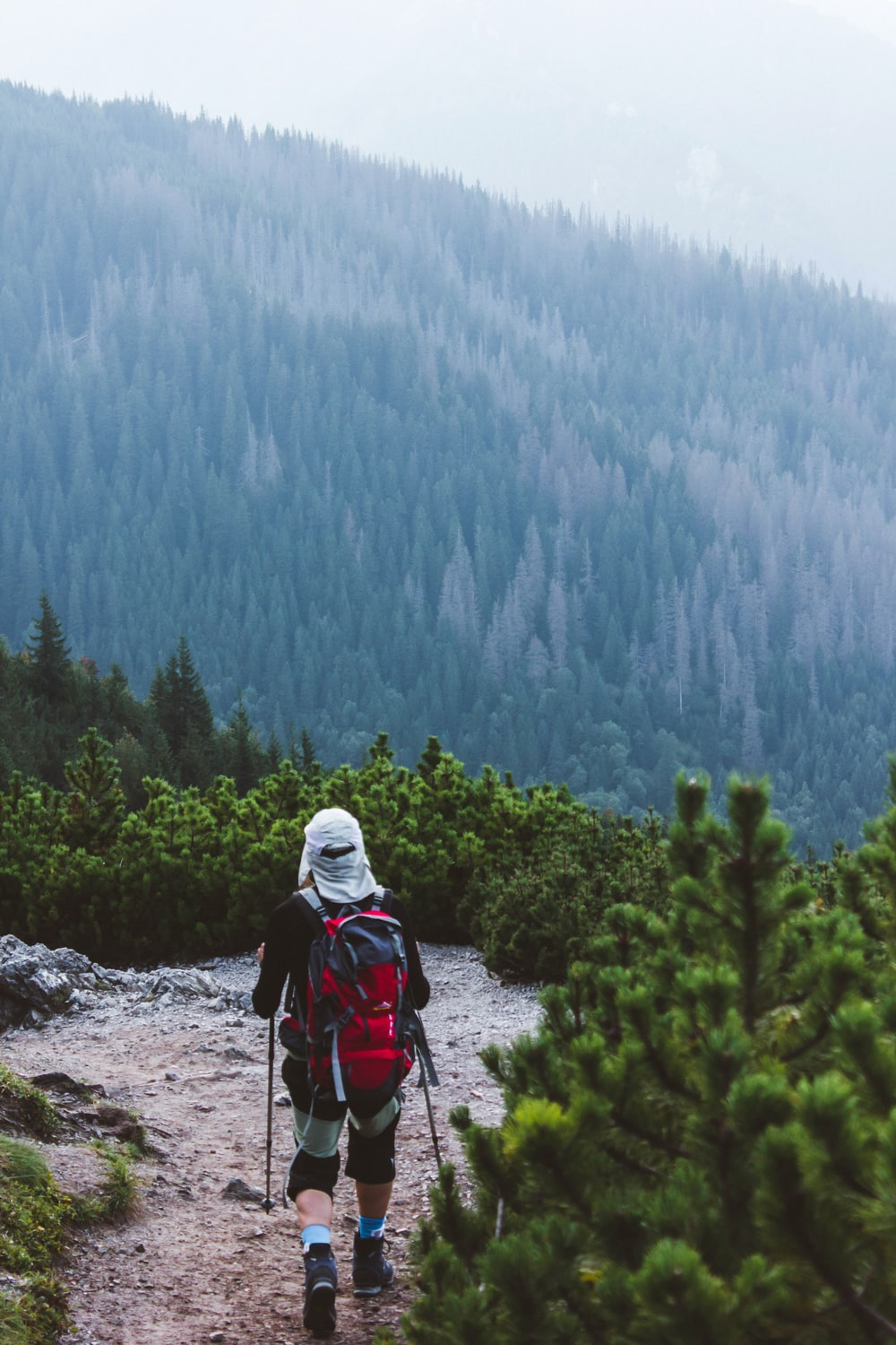 person in white hoodie and red backpack standing on rocky ground during daytime