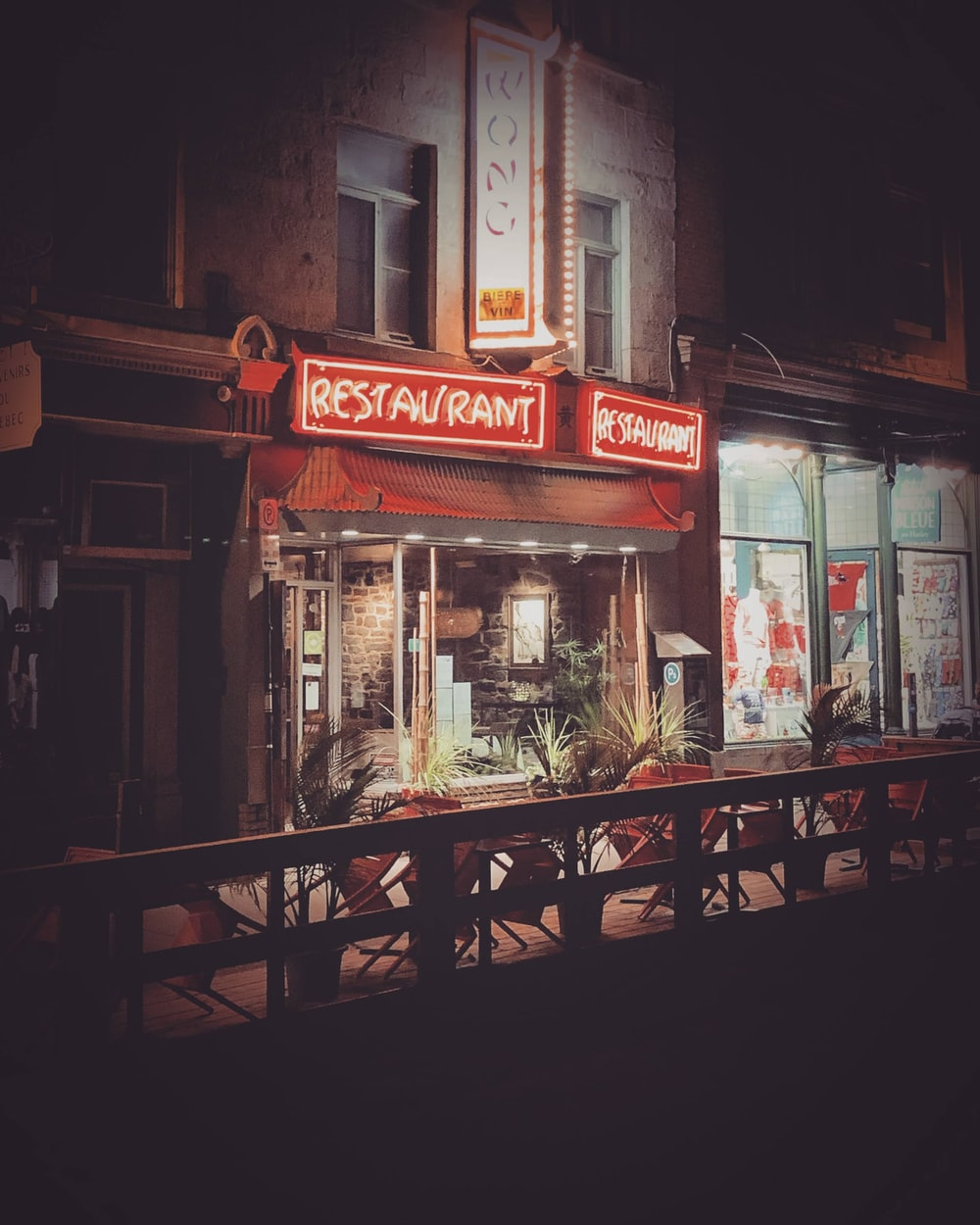 brown wooden chairs and tables in front of store during night time