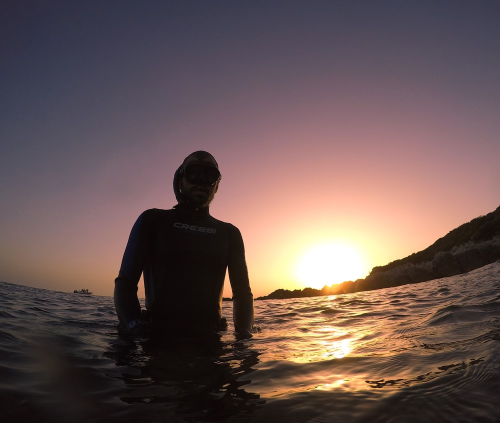 man in black tank top standing on water during sunset