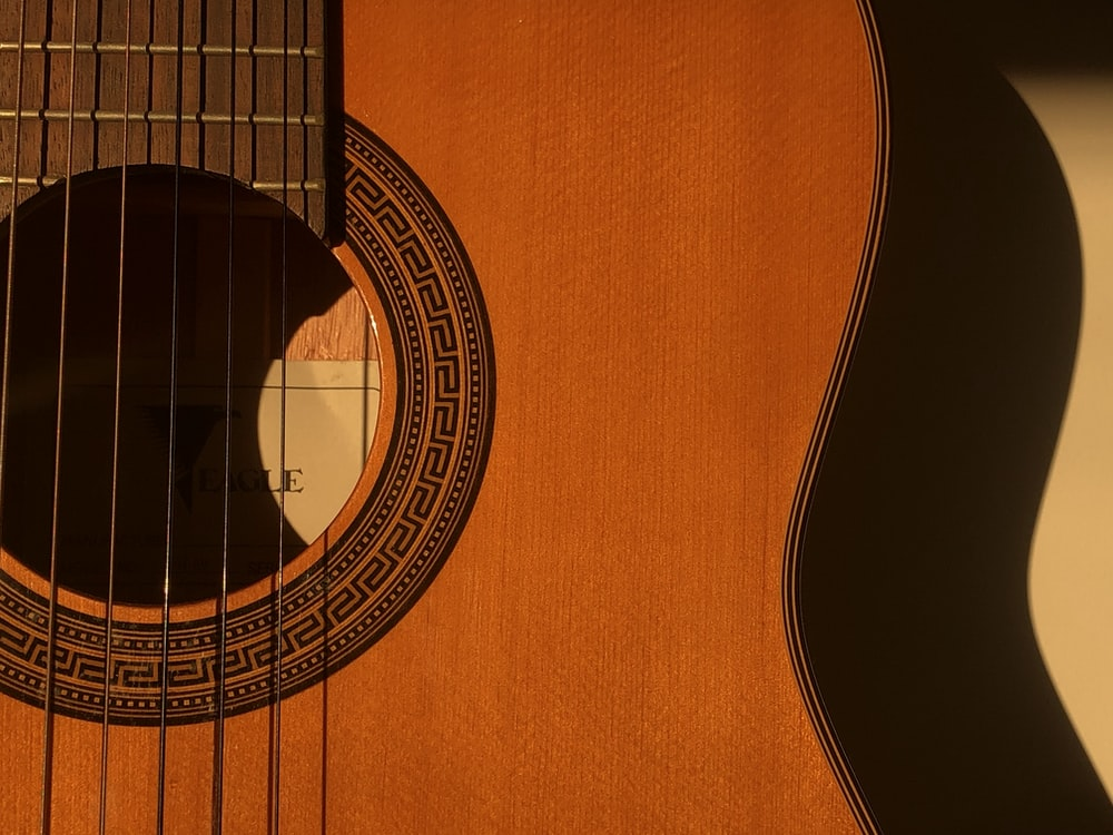 brown acoustic guitar on white textile