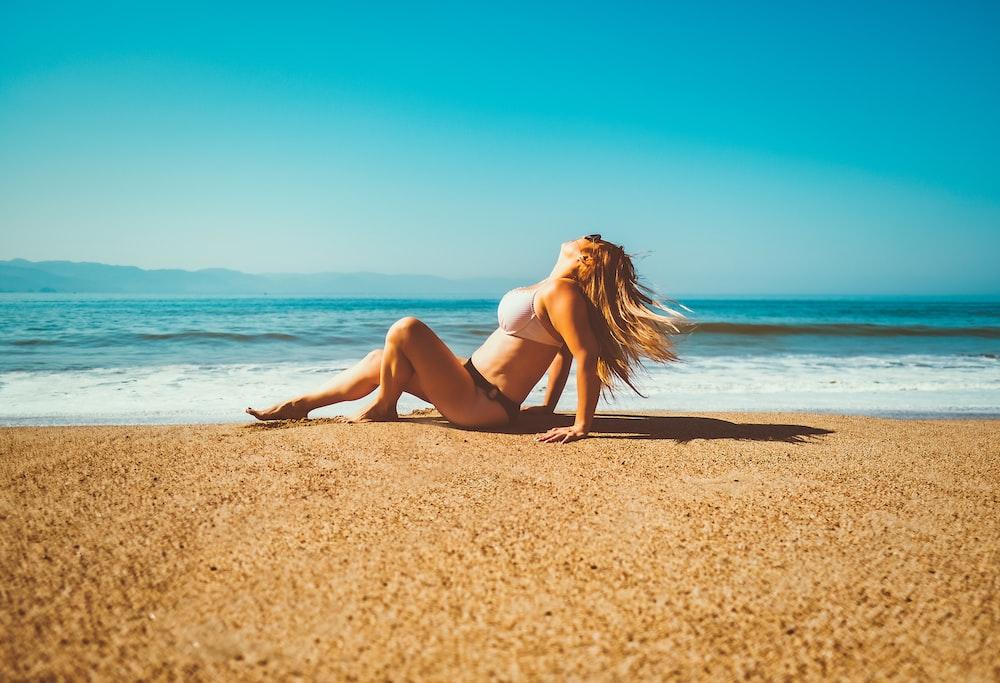 woman in white bikini lying on beach sand during daytime