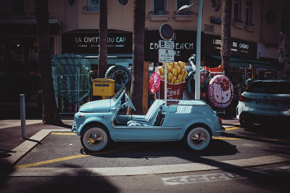 blue and white beetle car parked on sidewalk during daytime