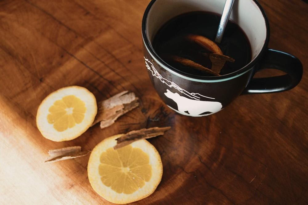 sliced lemon beside black ceramic mug