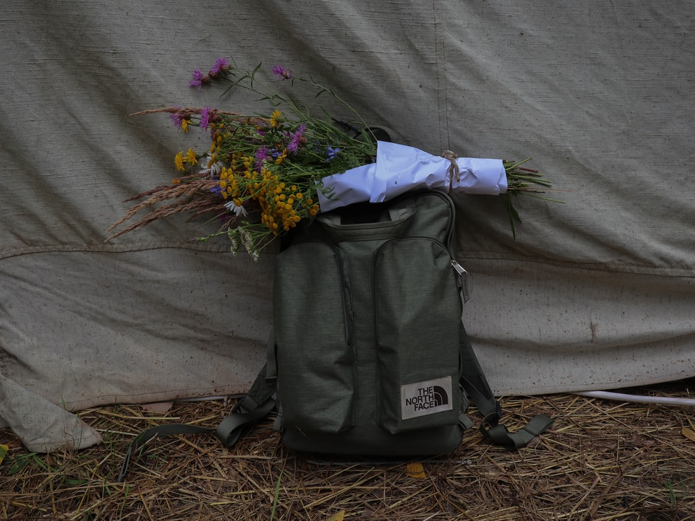 green and yellow flower bouquet on black and gray backpack