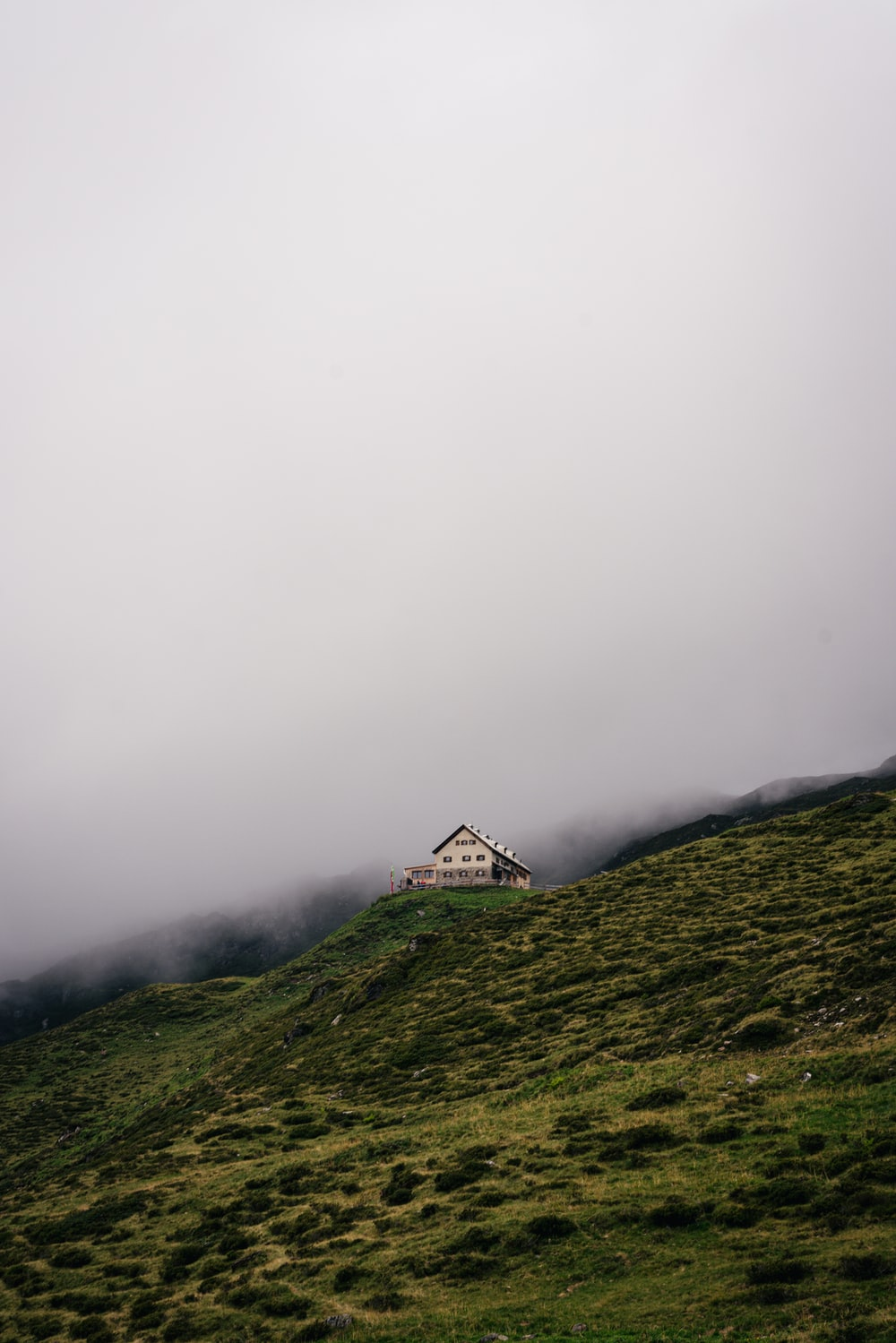 white and brown house on green grass field covered with fog
