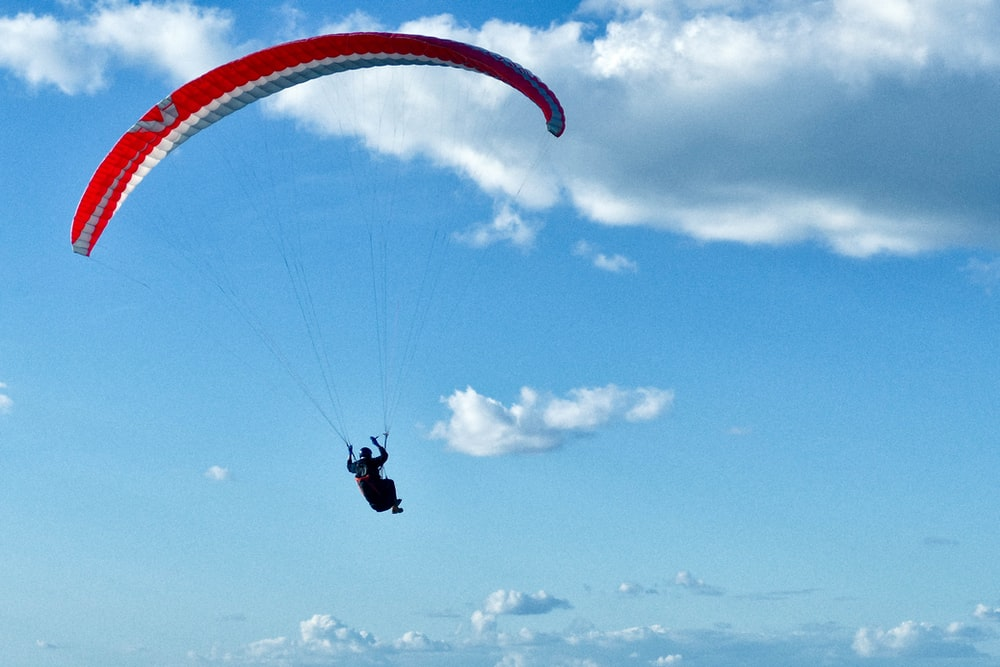 person in black and white parachute under blue sky during daytime