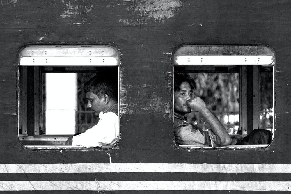 grayscale photo of man and woman sitting on train