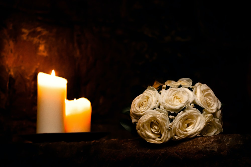 white rose flowers beside white candles