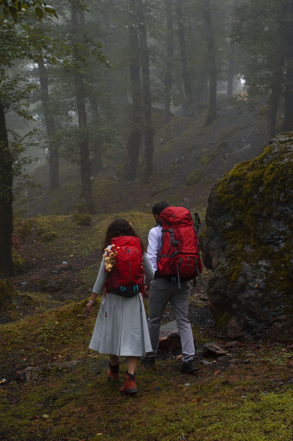 couple in red and black jackets walking on pathway