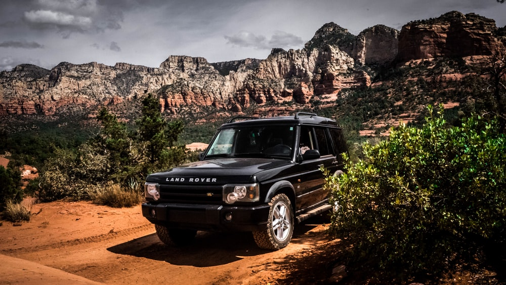 black mercedes benz g class suv on brown dirt road during daytime