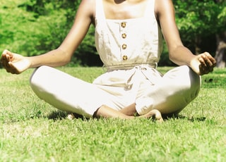 woman in white tank top sitting on green grass field during daytime