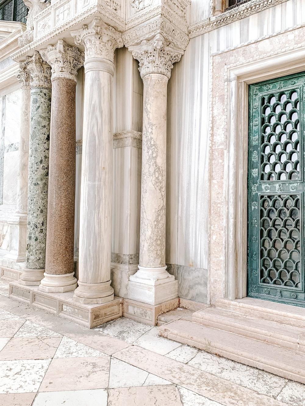 white concrete pillar near black metal window
