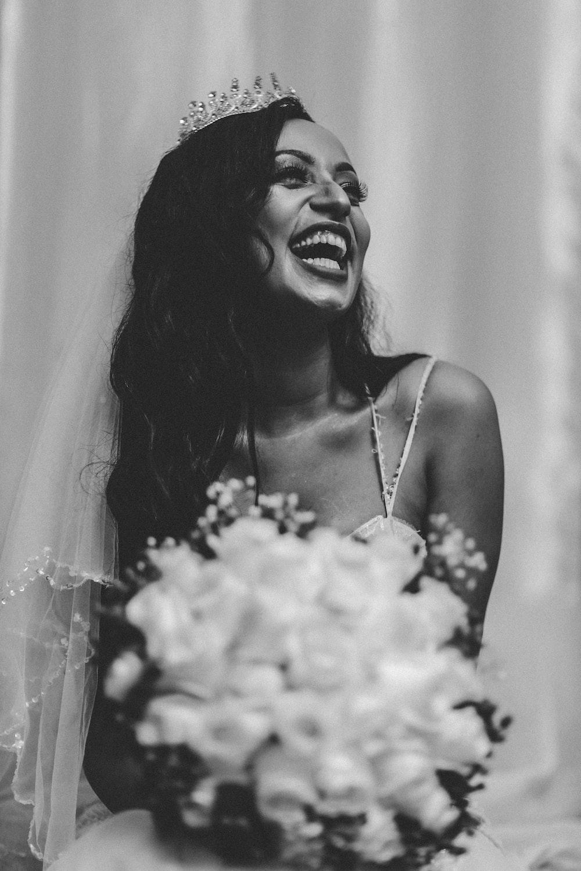 woman in white spaghetti strap top smiling