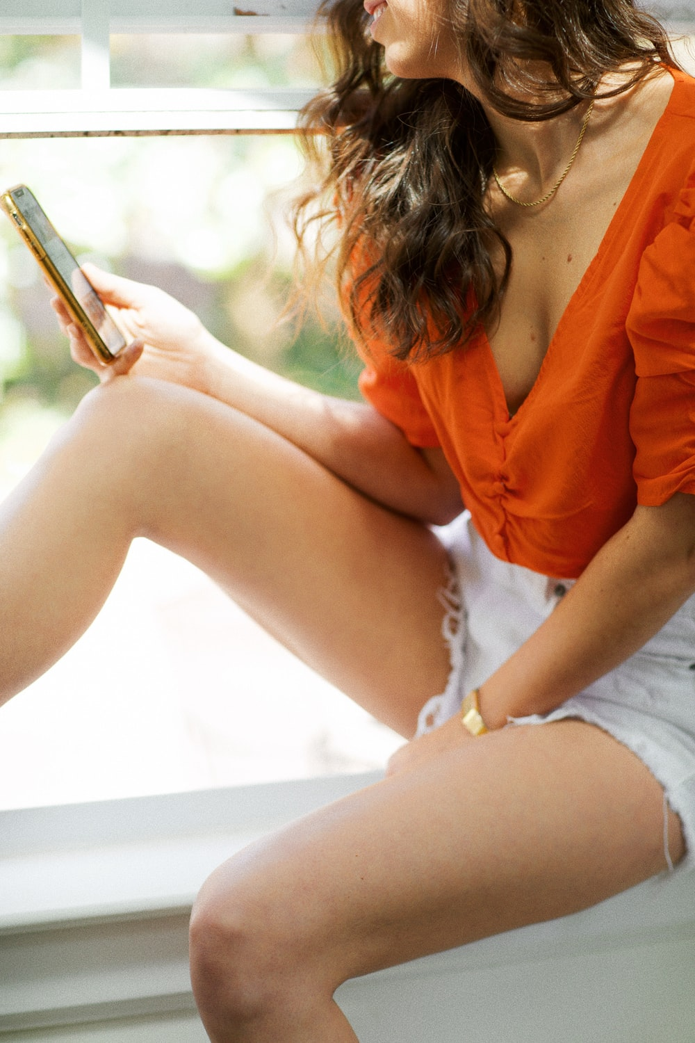 woman in orange long sleeve shirt and white shorts sitting on white bench