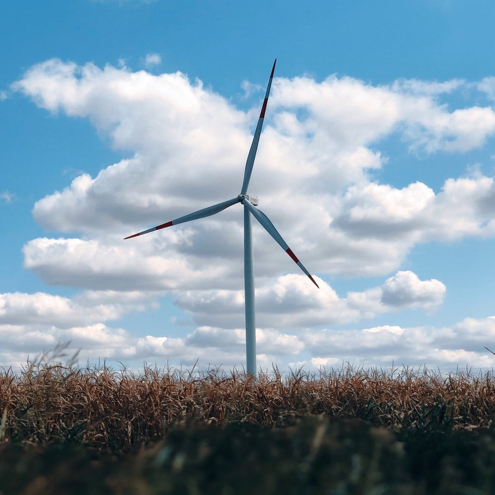 wind turbine on brown grass field under blue and white cloudy sky during daytime