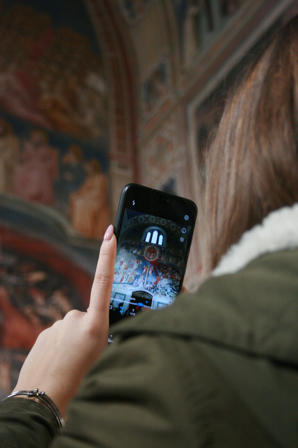 woman in white fur jacket holding black iphone 5