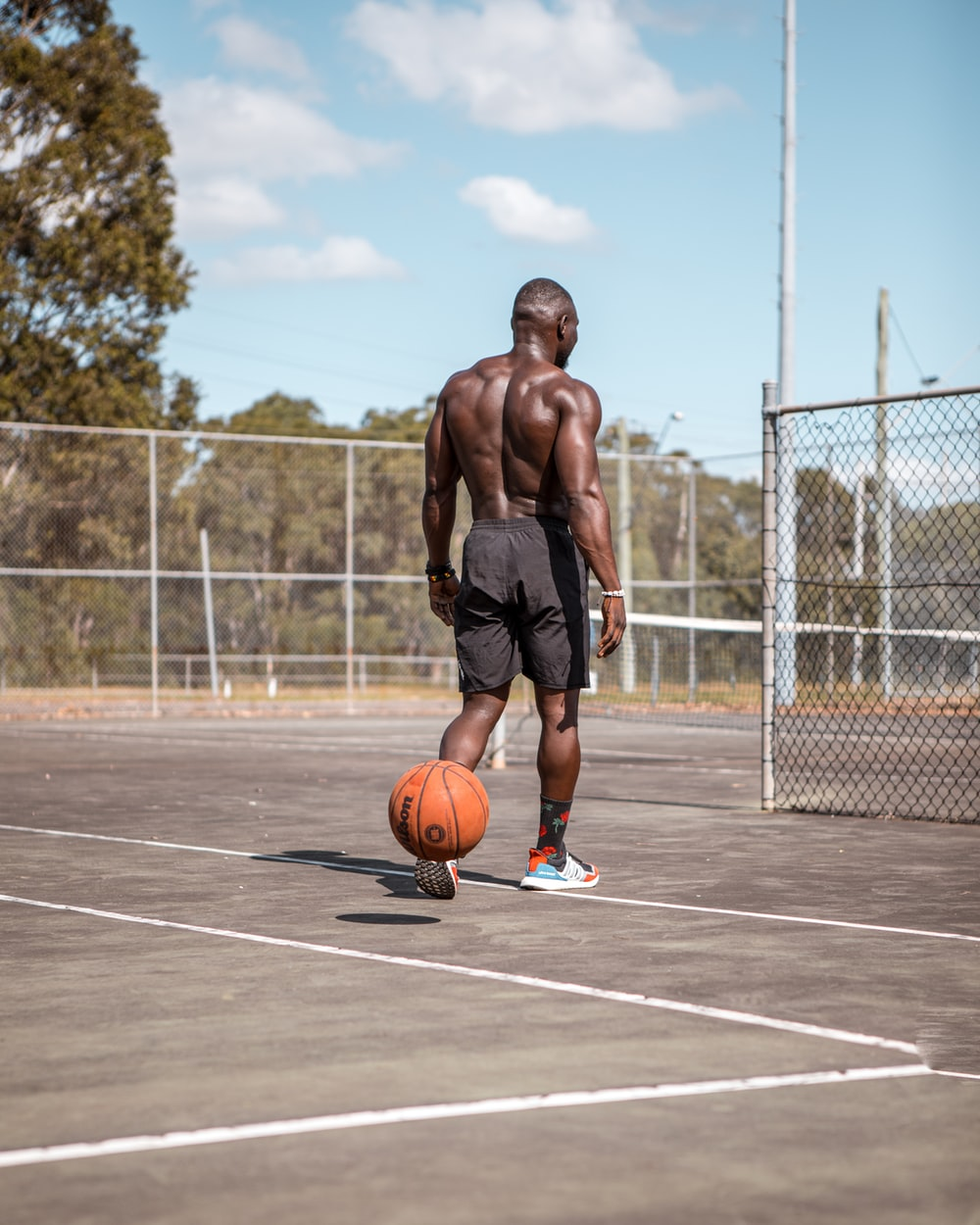man in black shorts running on basketball court