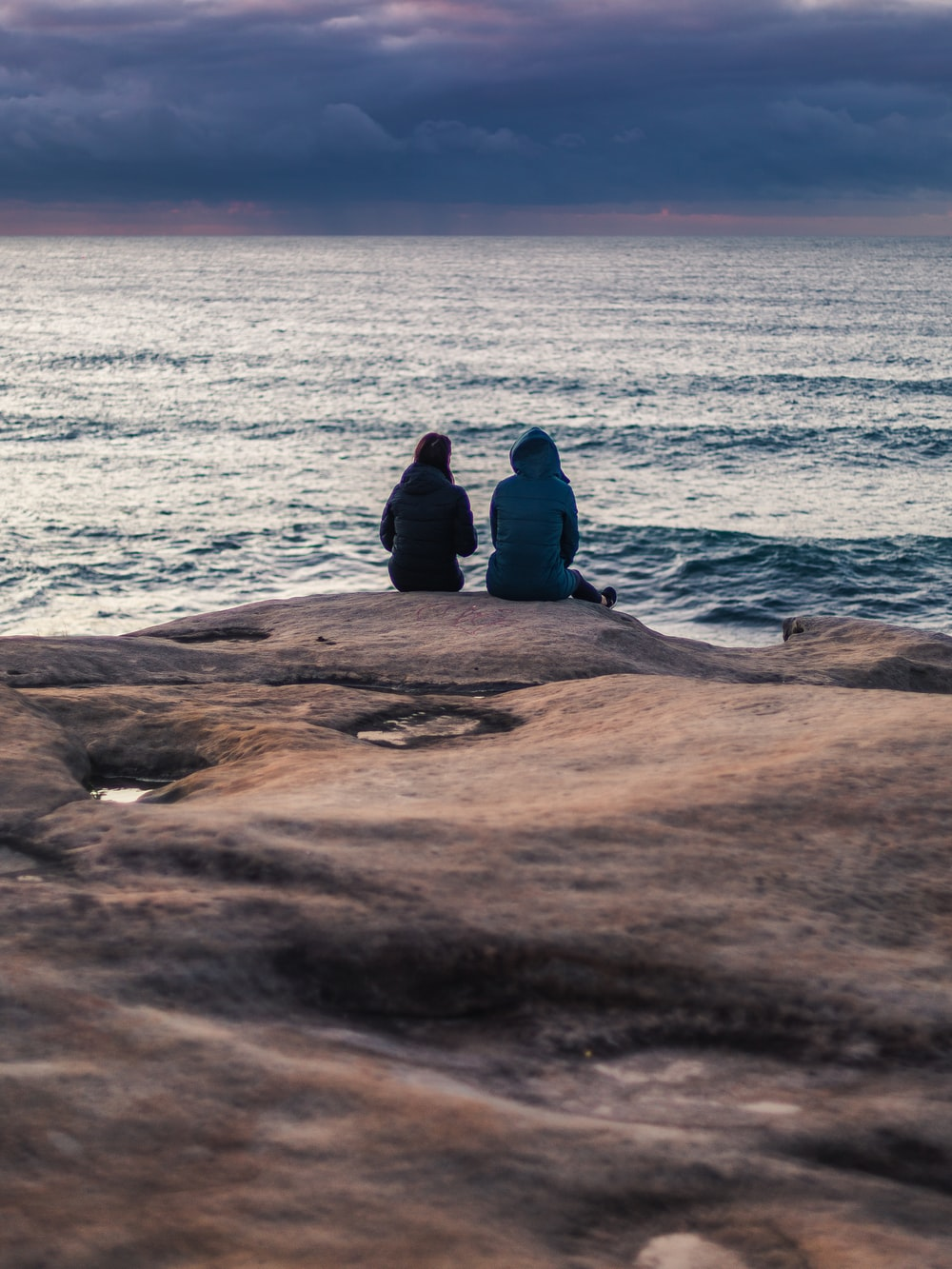 man in black jacket sitting on brown rock near sea during daytime